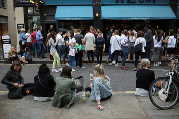 People drink cocktails on a street in central London