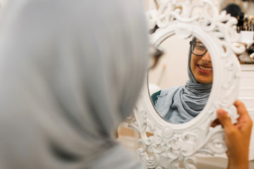 Muslim woman looks at herself in mirror after receiving Halal eyebrow treatment at Le'Jemalik Salon in New York