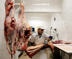 A butcher prepares meat at a shop in Sao Paulo