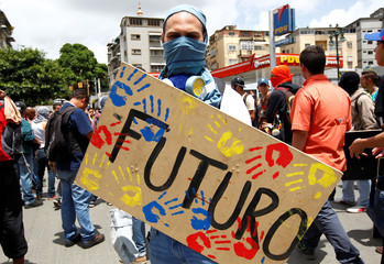 """A protester holds a makeshift shield reading """"Future"""" and with hand prints in the national colours during a rally against Venezuela's President Nicolas Maduro's government in Caracas,"""