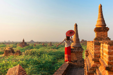 A girl with a traditional Burmese umbrella relaxing in an ancient temple during sunset, Bagan,Myanmar.Ancient temples in Bagan in sunny sunset.Young traveller enjoying a looking at Buddhist stupas.