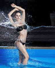Slim fashion model posing in the pool under the spray of water