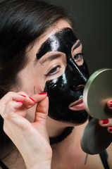 Close up of a beauty young woman taking off half of a black face mask looking at mirror