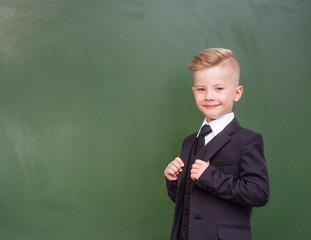 Happy boy in a suit standing near empty green chalkboard