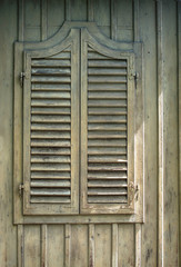 Old window with shutters.Window with closed shutters on the wall of vintage wooden house.