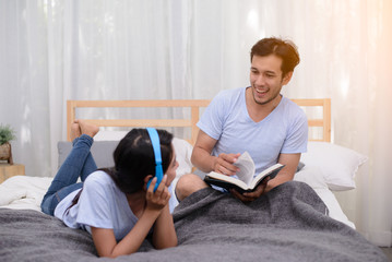Man reading a book while his wife listening a music in bedroom.
