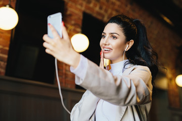 Brunette woman in white jacket having dark eyes with long eyelashes, full lips and healthy skin having good mood while resting in cafe listening to different tracks with earphones and making selfie
