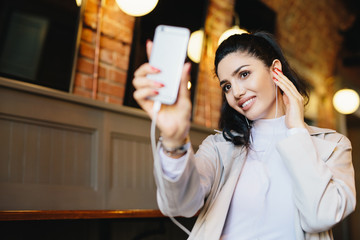 Attractive woman with dark hair, healthy skin and bright eyes holding smartphone in her hand making selfie and listening to music or audio book while resting in cafe. People and leisure concept