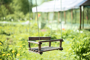 Wooden suspension swing in the nature