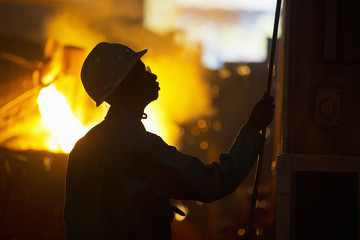 Silhouette Of Worker In Foundry With Molten Metal Being Poured