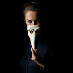 woman isolated on black hiding behind Venetian mask