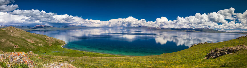 Panorama of mountain Son Kol lake. Beautiful clouds reflected in water. Kyrgyzstan.