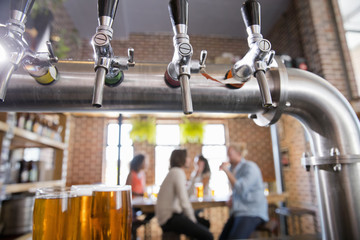 Close-up of beer taps at a bar, customers in the background