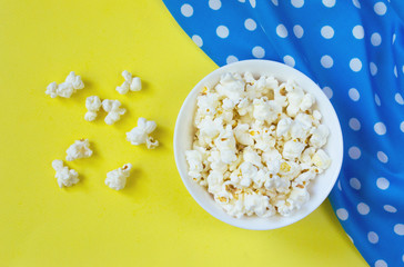 Popcorn in bowl on yellow background, retro style
