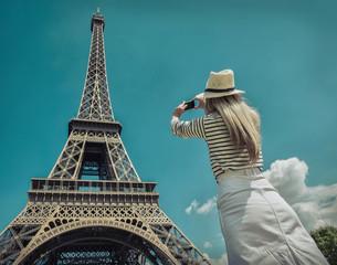 Woman tourist selfie near the Eiffel tower in Paris under sunlig