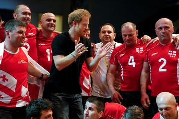 Britain's Prince Harry poses for a photo with the sitting volleyball team from Georgia during the Invictus Games in Orlando, Florida