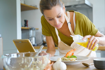 Young woman in kitchen testing recipe of asian dish
