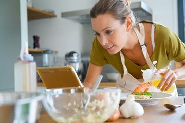 Woman in kitchen preparing dish, reading recipe on digital tablet