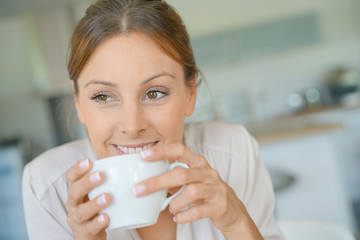 Portrait of beautiful woman at home drinking coffee