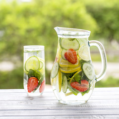 Dietary detox drink with lemon juice, red strawberry, cucumber and mint leaves in clear water with ice.