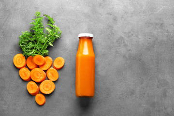 Bottle of fresh smoothie, carrot slices  on grey background