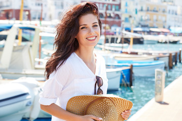 Beautiful young woman on vacation in a port in an Italian town. Summer concept