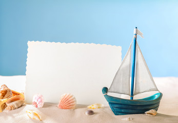 Blank card, toy ship and shells on sand against color background. Concept of travel and vacation