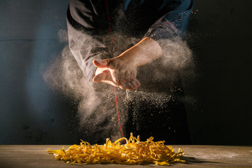 Chef adds wheat flour to the Italian ribbon-shaped pasta, before preparing the dish. Freeze motion effect. Strong contrast side lighting.