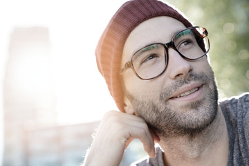 Hipster guy with eyeglasses and cap relaxing in park