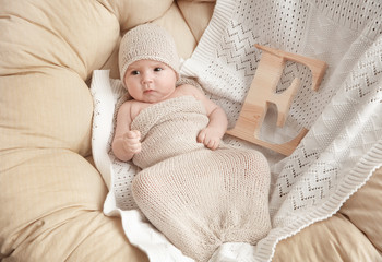 Cute baby with letter E lying on soft blanket in armchair. Choosing name concept