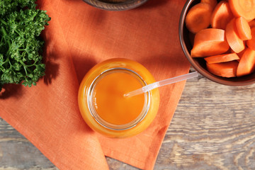 Jar of carrot juice on wooden table
