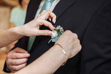 Woman pinning the boutonniere on the groom's jacket. Close up picture. Unrecognizable man. Horizontal format