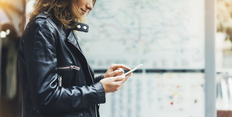 Fotomurales - Girl in leather jacket holding smart phone on background map light box in sun city, hipster using in female hands and texting mobile, glitter street lifestyle, tourist planing route in summer