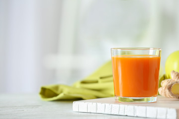Glass of carrot juice on light table