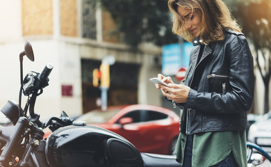 Girl in leather jacket holding smart phone on background motorcycle in sun city, hipster using in female hands and texting mobile, glitter street lifestyle, tourist planing route in summer concept Fotomurales