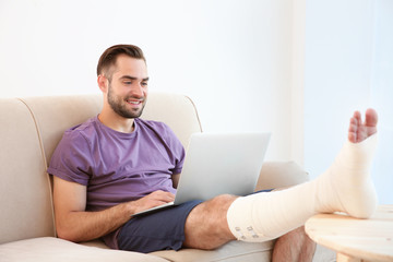 Handsome young man with laptop and bandaged leg sitting on sofa at home