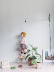 Kleines Mädchen im Tutu steht auf Stuhl in der Wohnung