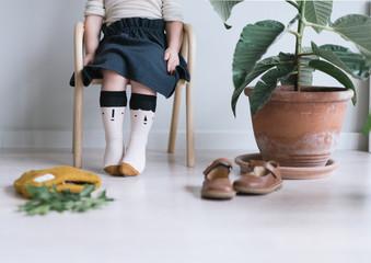 Kleines Mädchen mit Roch und lustigen Socken