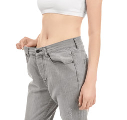 Beautiful young woman in oversized jeans on white background, closeup. Diet concept