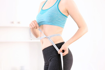 Beautiful young woman with measuring tape at home. Diet concept
