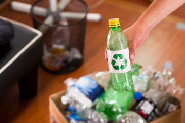 Close up of a hand putting a plastic bottle with a printed sign of recycling in front, inside of a cardboard box full of plastic, recycle and safe the world from global warming concept