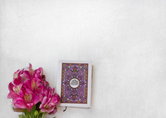 Holy Quran with flowers on white wooden background