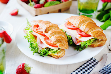 Breakfast, business lunch, sandwiches croissant with ham, cheese, sauce, lettuce, tomato and strawberry mint ice-cold cocktail on a light background