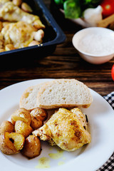 Hearty and delicious dinner, baked chicken legs and thighs with potatoes, onions, tomatoes, spices, herbs and white bread on a dark wooden background