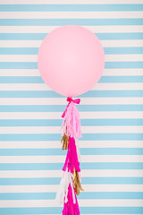 Pink balloon on a striped background in room decorated for birthday party