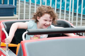 Young toddler girl having fun on boardwalk amusement ride