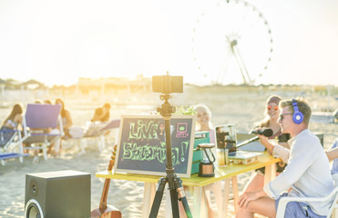 Group of young people making a video live streaming from beach party at sunset - Man vlogger using phone camera for filming festival event - New technology trends social concept - Focus on smartphone