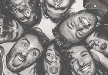 Bottom view of young friends making funny faces on camera - Happy people having fun making selfie  - Focus on top right man - Black and white editing - Friendship concept - Warm contrast filter