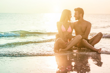 Young couple in love kissing on the beach at sunset - Two lovers having tender moments in summer vacation - Romantic concept - Soft focus on them - Radial purple and blue filter editing