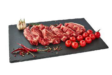Fresh raw beef steaks with pepper and tomatoes on black slate board. Isolated over white
